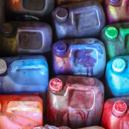 Kanister mit unterschiedlichen Farben bei SMOLart. Die Farben mischen die MitarbeiterInnen selbst zusammen.