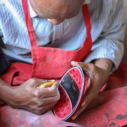 Der Specksteinteller erhält nach und nach seine umfangreichen Verzierungen. Der Künstler graviert mit seiner Messerspitze die Muster.