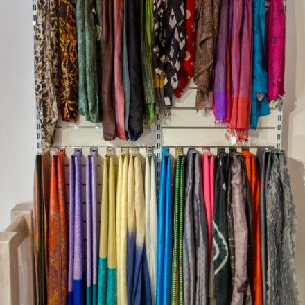 Schals geordnet an der Wand präsentiert in der oberen Etage.