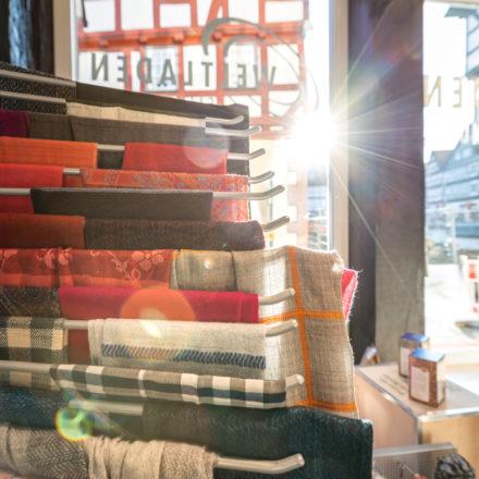Die Schals sind auf Stangen präsentiert. Diese sind als Fächer am Regal montiert.