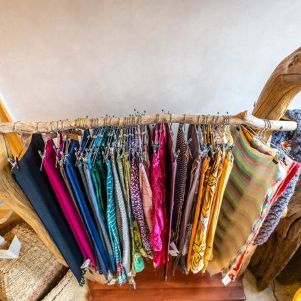 Die Schals sind mit Hosenbügeln aufgehängt und farblich sortiert.