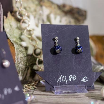 Ohrhänger und -stecker werden mit dunklem Kartonpapier präsentiert.