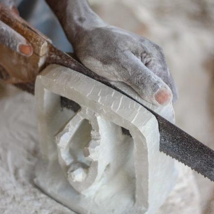 Nachdem die grobe Figur steht, sägt der Handwerker die Buchstütze in zwei Stücke.