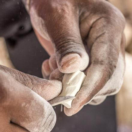 Schicht für Schicht formt die Messerklinge den Stein zu einer Schachfigur. Der Handwerker geht sehr behutsam vor.