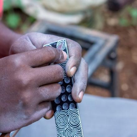 """Beim Gravieren dieses Räucherstäbchenhalters kommt die ursprünglich weiße Farbe des Specksteins wieder zum Vorschein. Der Handwerker von Undugu """"malt"""" hier Kreise als Muster auf."""