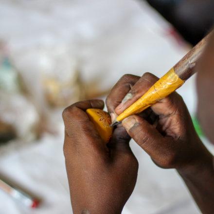 Die Mitarbeiter fertigen ihre Werkzeuge selbst. Hier verziert ein Mitarbeiter von SMOLart das Specksteinherz mit einer Messerspitze.